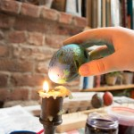 After the eggs dry, hold them up to the flame to melt the wax. Wipe it away and voila.